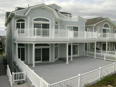 Back of home showing main deck  off of living area and from master suite