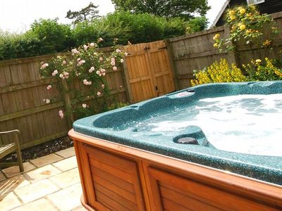Enclosed hot tub area beside the garden