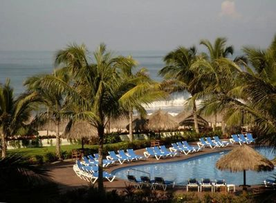 Large swimming pool with lounge chairs next to the ocean seen from our balcony