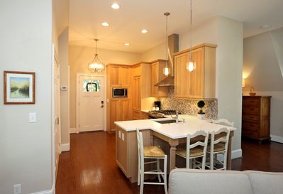 """Kitchen with dining """"table"""" as seen from the living room.  Dimmers on lights..."""