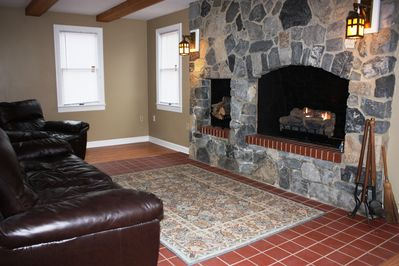 Massive stone fireplace and gas fire logs with leather sofa in great room