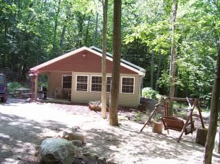 View of cabin and swing by fire pit
