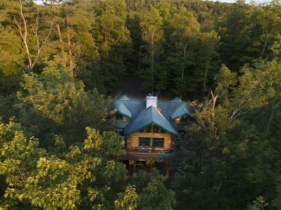 3-story handcrafted log mansion tucked into a private, wooded lakefront spot.