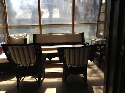 Screened in porch with classic wicker furniture.
