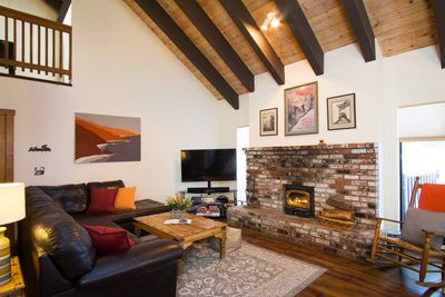 Spacious great room with high ceilings and wood burning fireplace