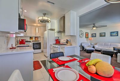 Red appliances and decor accent the white-themed dining and kitchen areas.