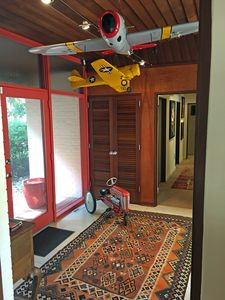 Foyer with vintage model planes and a 50's peddle tractor, Kilim rug.