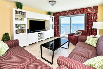 Living room with ocean view and newer tile floor, end tables, couch & sofa bed!
