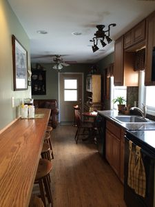Galley kitchen with granite counters, maple cabinets, & custom breakfast bar