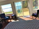 Master bedroom with fantastic ocean views and queen bed and patio door to open deck to watch the whales and wild life from.