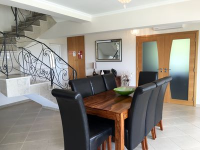 Open plan dining area with garden view and feature staircase