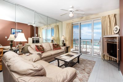 "With the idyllic huge leather couch and loveseat, it is screaming ""COMFORTABLE!"" Amazing views from the 5th floor with the entry to the beach front balcony."