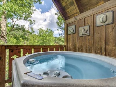 The outdoor hot tub… ahhh! - As well as a gas grill, rocking chairs, and a table for alfresco snacking, the large back deck includes a spacious hot tub. What better way to end the day than with a soothing soak under the stars?