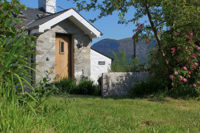 The side garden, table and chairs and lawn with Mountain Views of Snowdonia