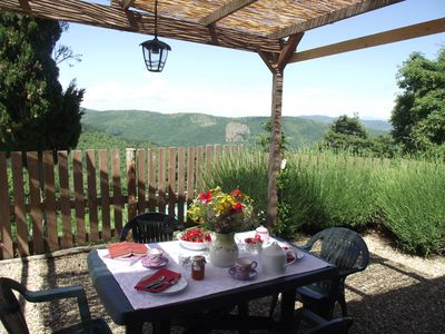 A table under a gazibo with view on the hills
