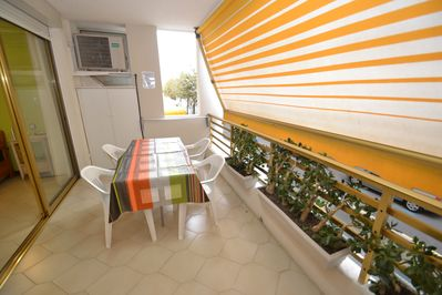 Beautiful furnished terrace with rolling sun blind, table, chairs and a closet.
