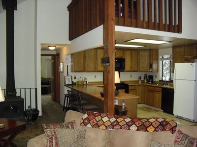 looking from living room back to kitchen and breakfast bar seating