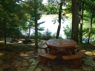 Fire pit and picnic table below log cabin along lakeshore