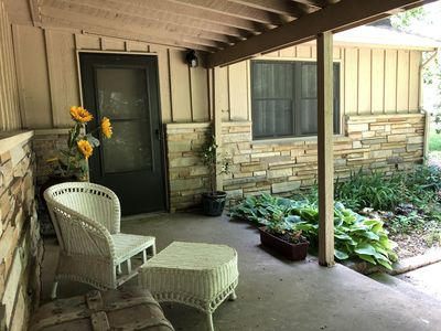 Covered front porch w seating area. Enjoy the front garden and quiet atmosphere.