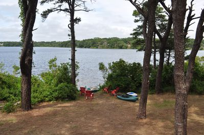 View from the back deck with Adirondack chairs, kayaks, and pedal boat