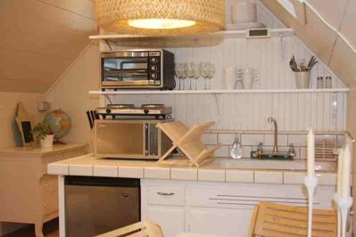 Mini-kitchen with toaster oven, half fridge, microwave, and 2-burner hot plate