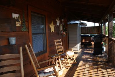 view of back deck, rocking chairs, new gas grill, hot tub
