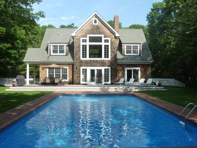 Back of house with large deck, brick patio  and 20' x 40' heated pool.