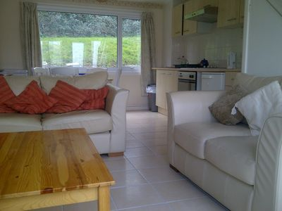 Open plan lounge/kitchen/dining room with comfortable sofas.