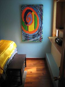 Bedroom with comfy queen bed and lovely natural cherry wood floors. Original art