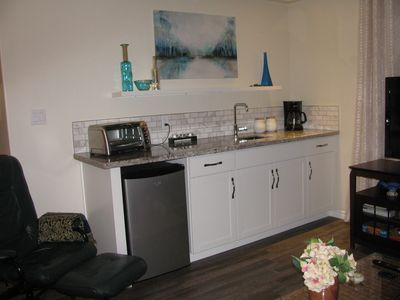 Kitchenette complete with toaster/oven, fridge, coffee maker, kettle, and dishes