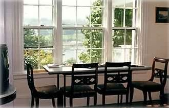 Duplex dining room table .Large window with  Rockport Harbor view