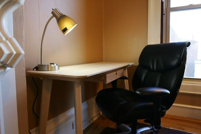 Desk with outlet-equipped lamp. Comfortable chair for working.
