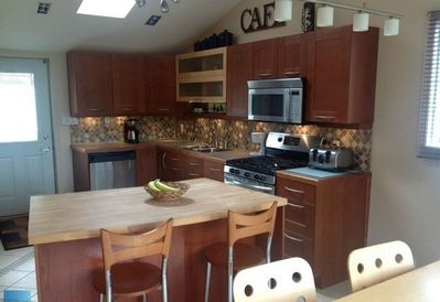 Main floor kitchen featuring stainless appliances, vaulted ceilings and walk out decks