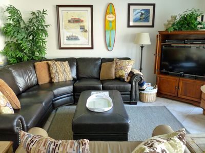 Comfortable Living Room, with leather sectional and love seat, and flatscreen TV