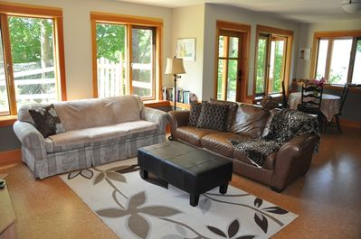 Living room has 2 comfy couches and a glider rocking chair with foot stool