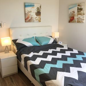 The master bedroom with a queen size bed, quality linen and ocean views.