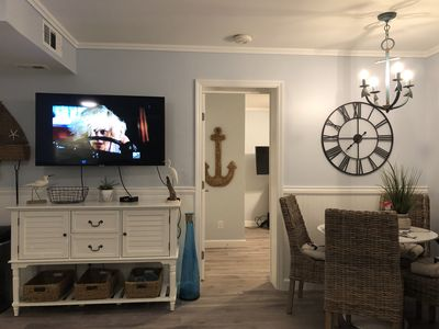 """Living room area with 50"""" flat screen smart tv, next to dining room"""