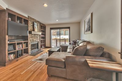 Entry into Spacious Living Room with Comfortable Seating, Smart TV and Gas Assist Fireplace with Beautiful Hardwood Floors