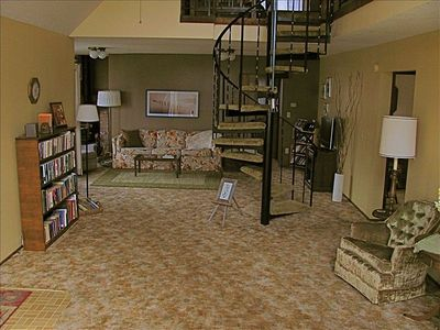Open living area with spiral stairs to loft.