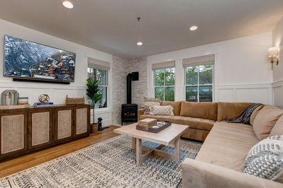 """Main Level Living Room with a Large Sectional Sofa, Gas Pot Belly Stove, 55"""" Smart TV with Xfinity Cable"""