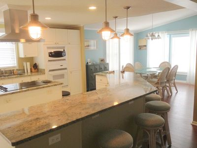 Fully renovated kitchen with granite countertops, wrap around bar area and drop down/recessed lighting on dimmers.