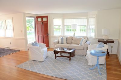 Family room with new comfortable slipcovered sofa and drum chairs