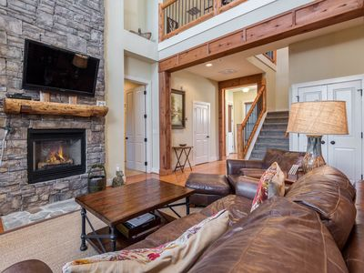 Large Living Room with Stacked Stone Fireplace and Plenty of Seating Options
