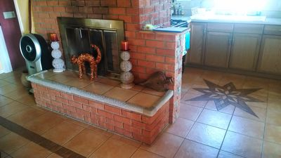 Living room fireplace and beautiful tiling design in kitchen floor.