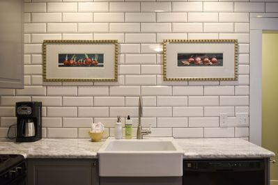 Kitchen - Large farm style sink with dishwasher and beautiful white subway tile