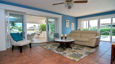Family room with sliders to the pool and the waterfront screened lanai.
