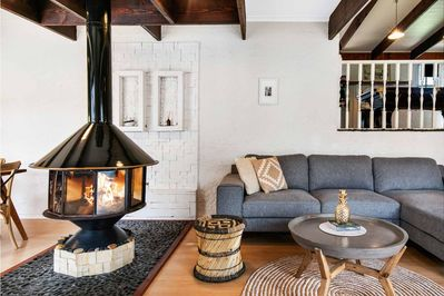 The main living area has a comfy modular couch and central fireplace
