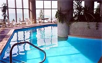 Heated Indoor Pool with waterfall next to sports center--first floor of building