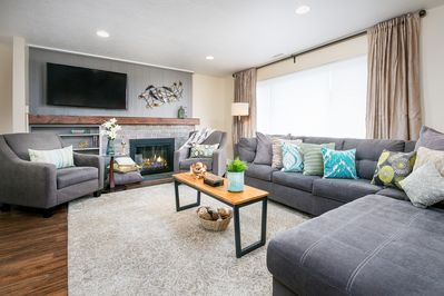 """Living Room - Welcome to Salt Lake City! The great room provides a large sectional with a queen-size pull-out bed and 54"""" smart TV. (Please note this fireplace is not operational.)"""