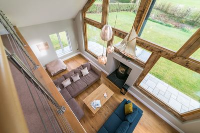Spacious double height open plan living room with log burner